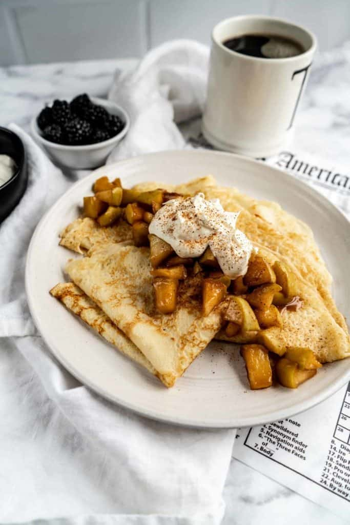 apple cinnamon crepes on plate with whipped cream served with coffee and fruit
