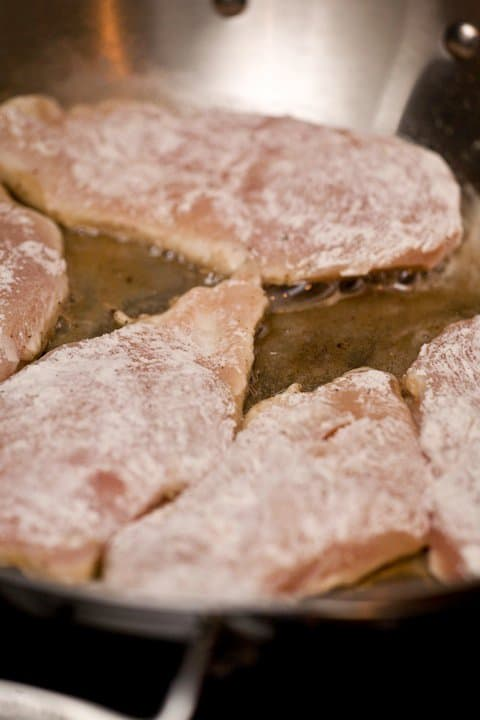 lightly floured chicken breasts in saute pan