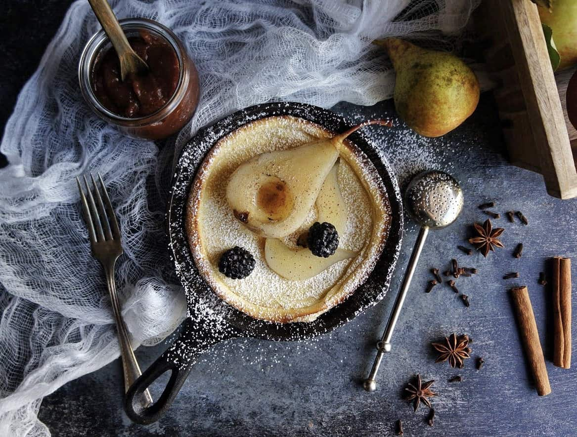 dutch baby pancake with poached pear and powdered sugar