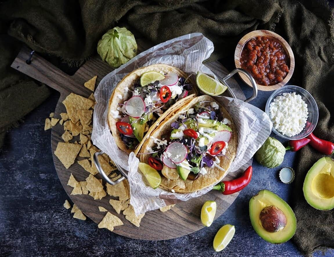 portobello mushroom tacos in a dish surrounded by salsa and avocado