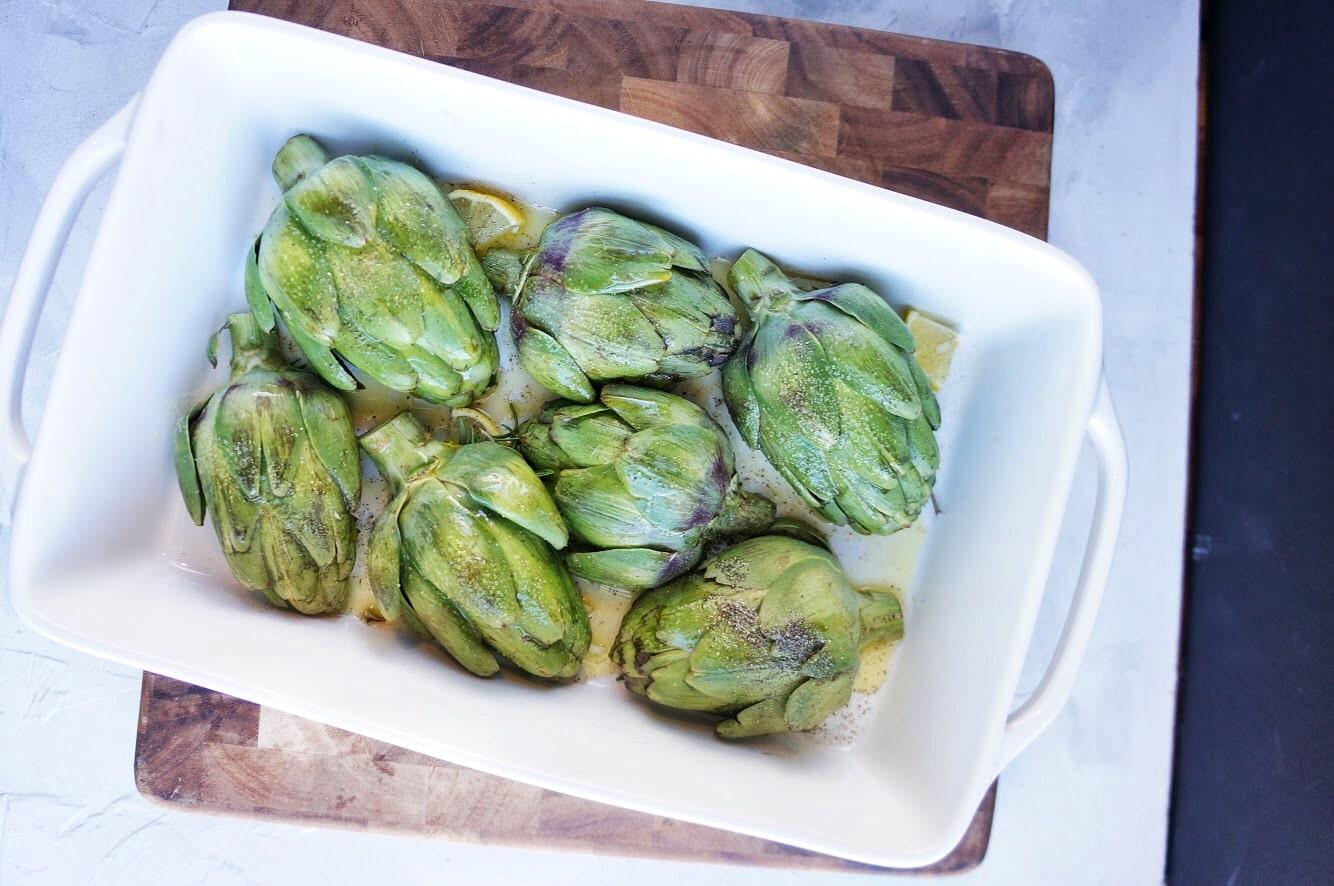 artichokes ready to roast in baking dish
