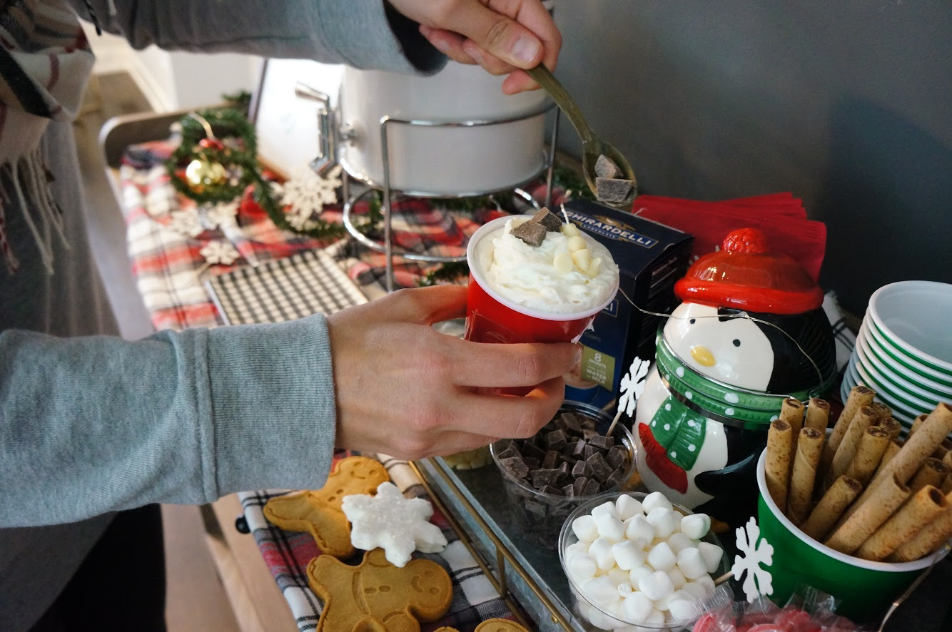 someone topping their hot cocoa at the hot cocoa bar