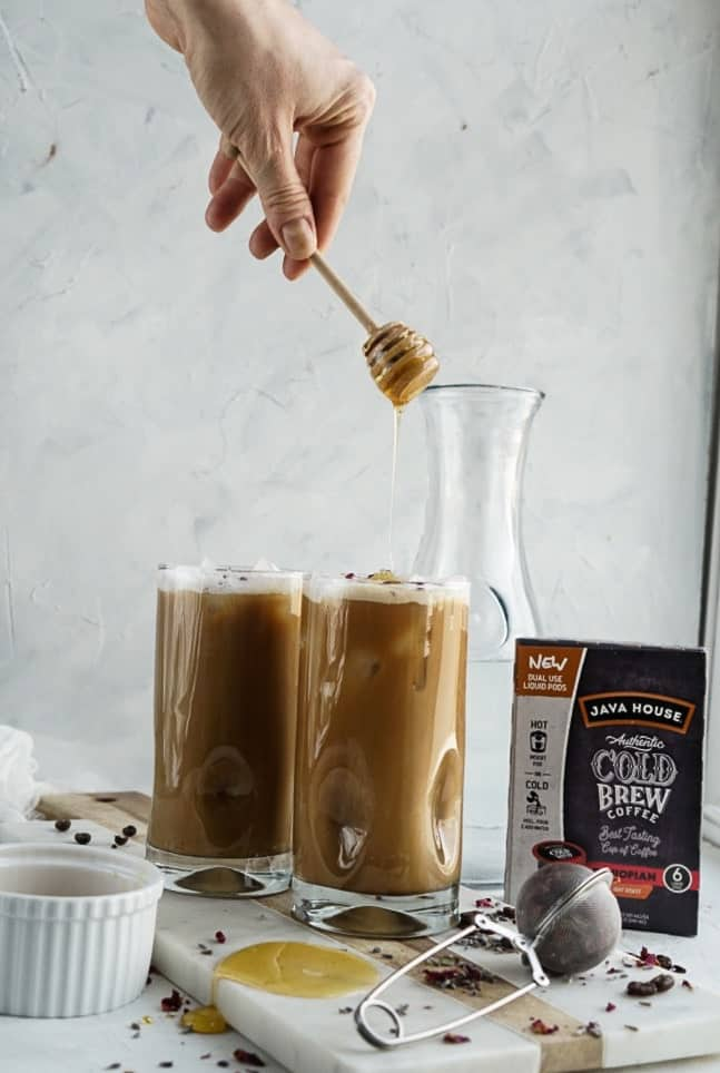 pouring honey into Iced Lavender Cold Brew Latte