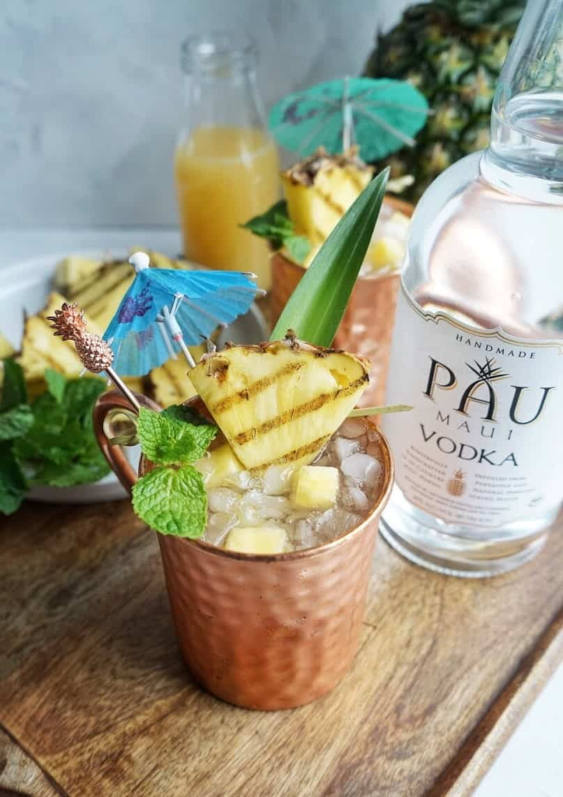 grilled pineapple mule garnished with cocktail umbrella