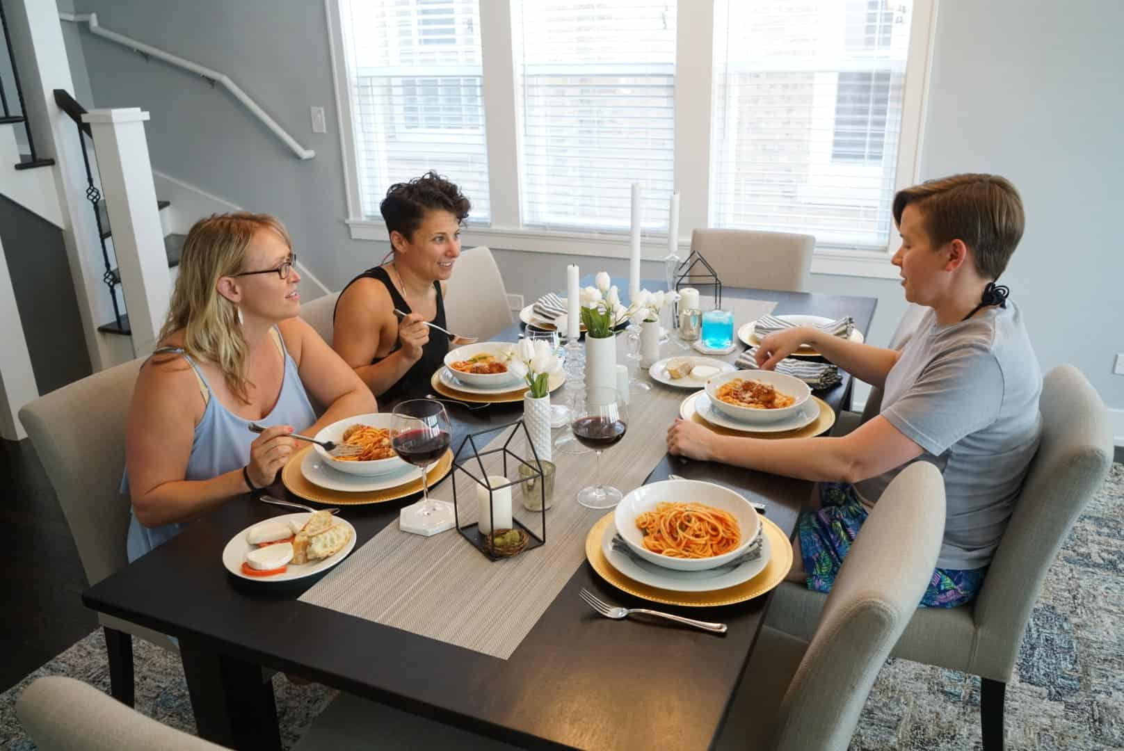 friends seated at dining table with Spaghetto al Pomodoro