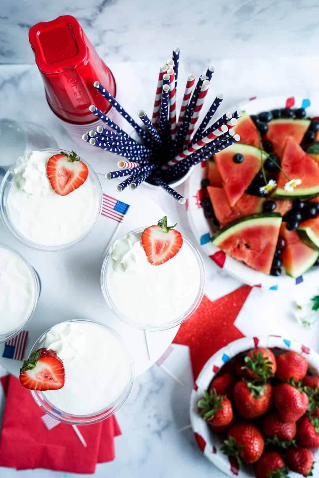 Stars and Stripes Frozen Yogurt Cups with sliced watermelon and strawberries in bowls
