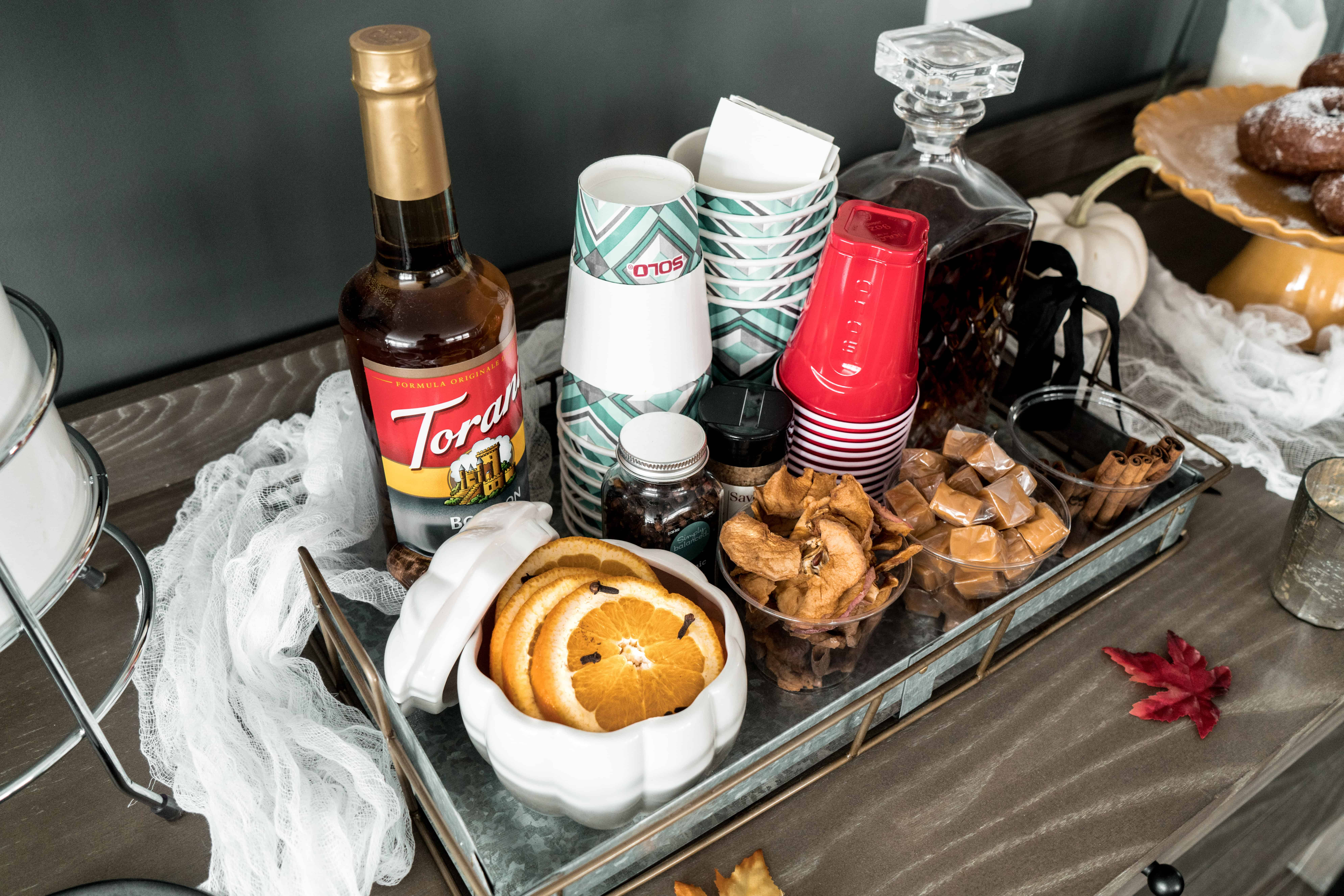 Hot apple cider bar toppings and cups in tray