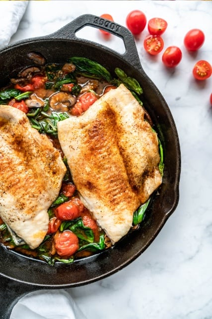 whitefish in pan with spinach and tomatoes
