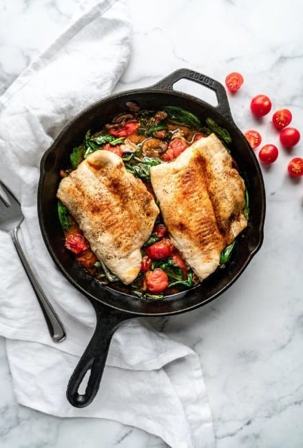 air fried white fish in pan with spinach and tomatoes