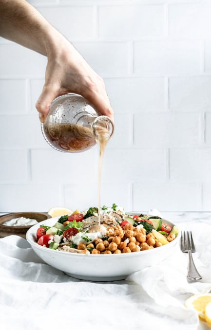salad dressing being poured on greek chicken bowl