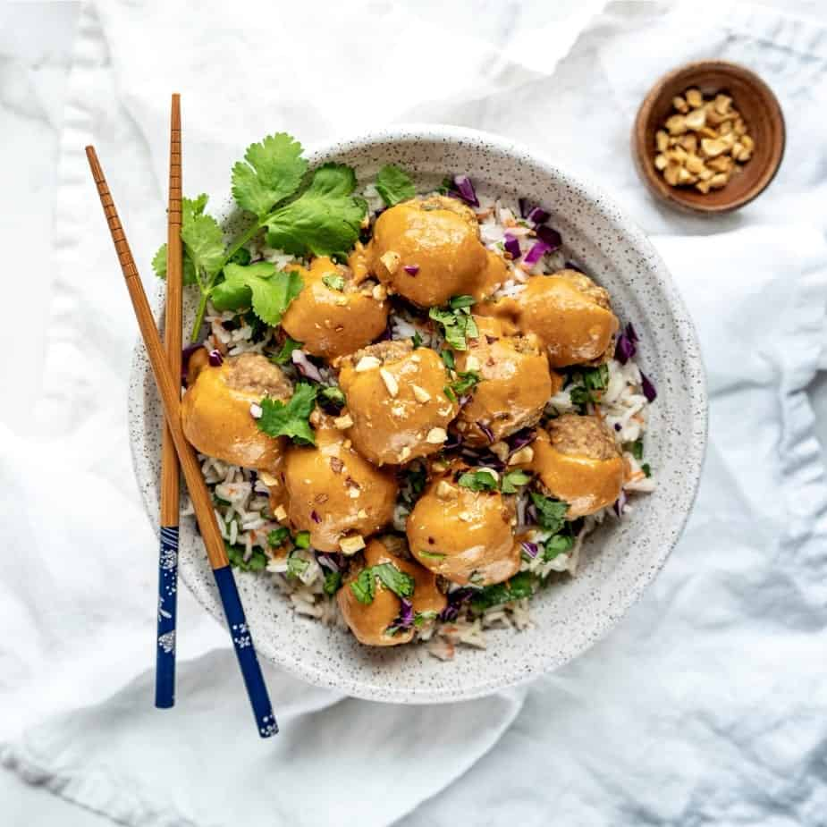 cooked asian turkey meatballs with peanut sauce and chopsticks
