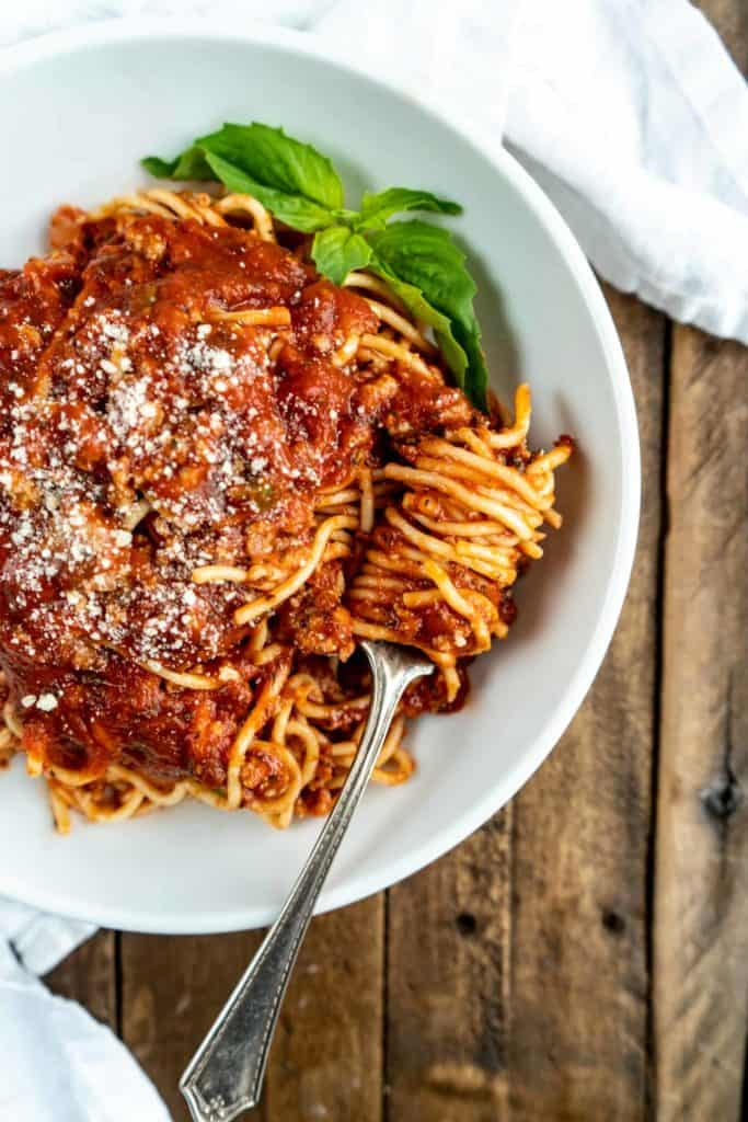 spaghetti bolognese in bowl with pasta twirled around fork