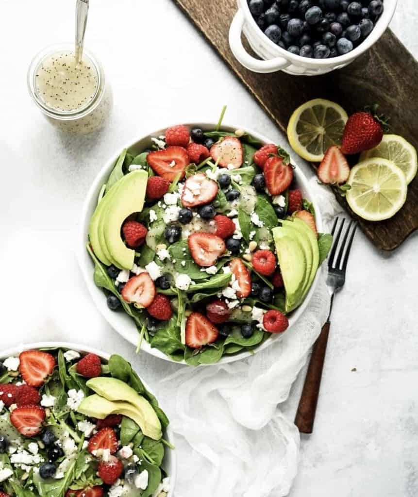 strawberry and spinach salad with fresh berries and avocado in bowl