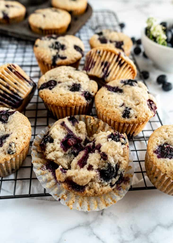 bakery style blueberry muffins close up on cooling rack, one muffin cut in half