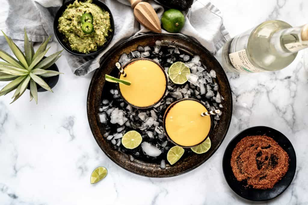 mango ginger margarita on drink tray with limes