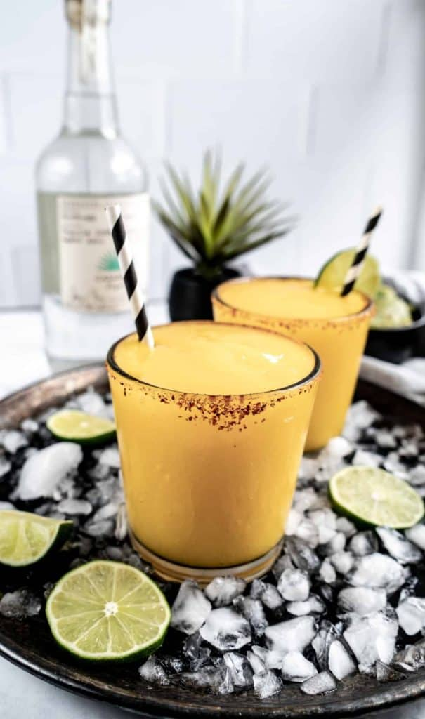 mango ginger margarita on drink tray with ice and limes
