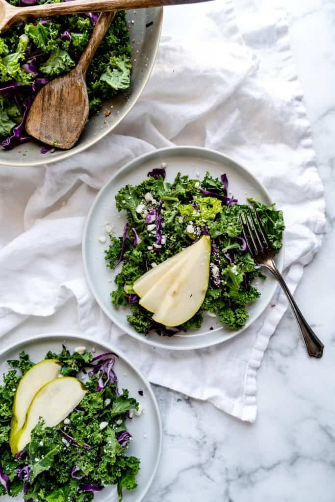 kale salad plated with sliced pear