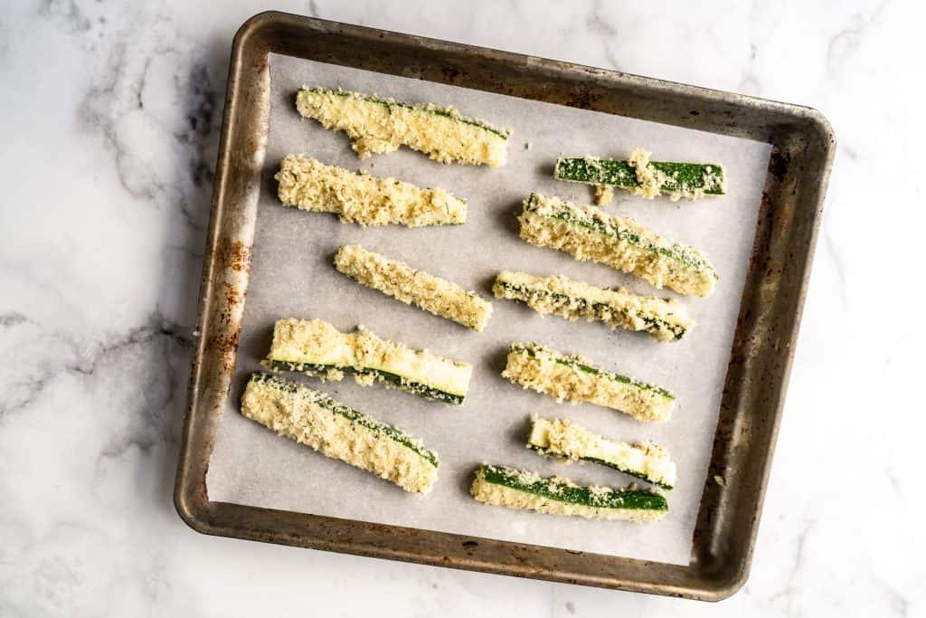 raw zucchini fries on baking sheet