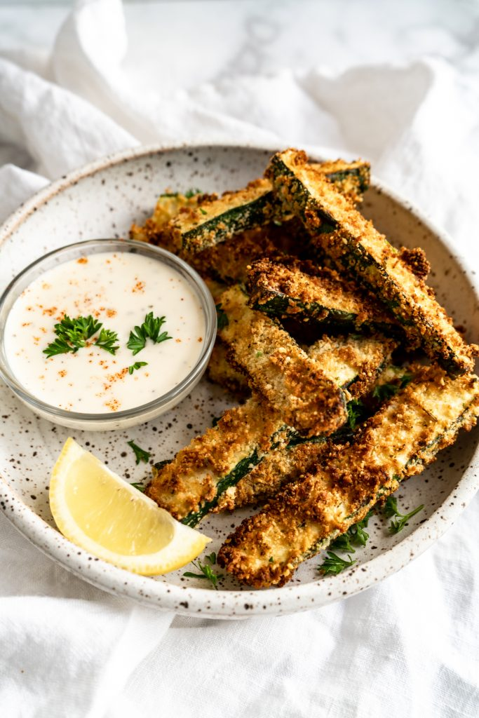 zucchini fries in bowl with dipping sauce and lemon wedge