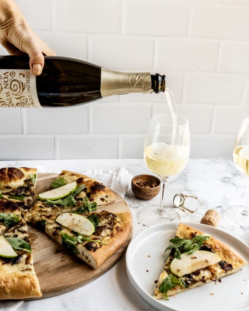 Gruyère and Caramelized Onion pizza sliced on cutting board with a hand pouring wine into glass