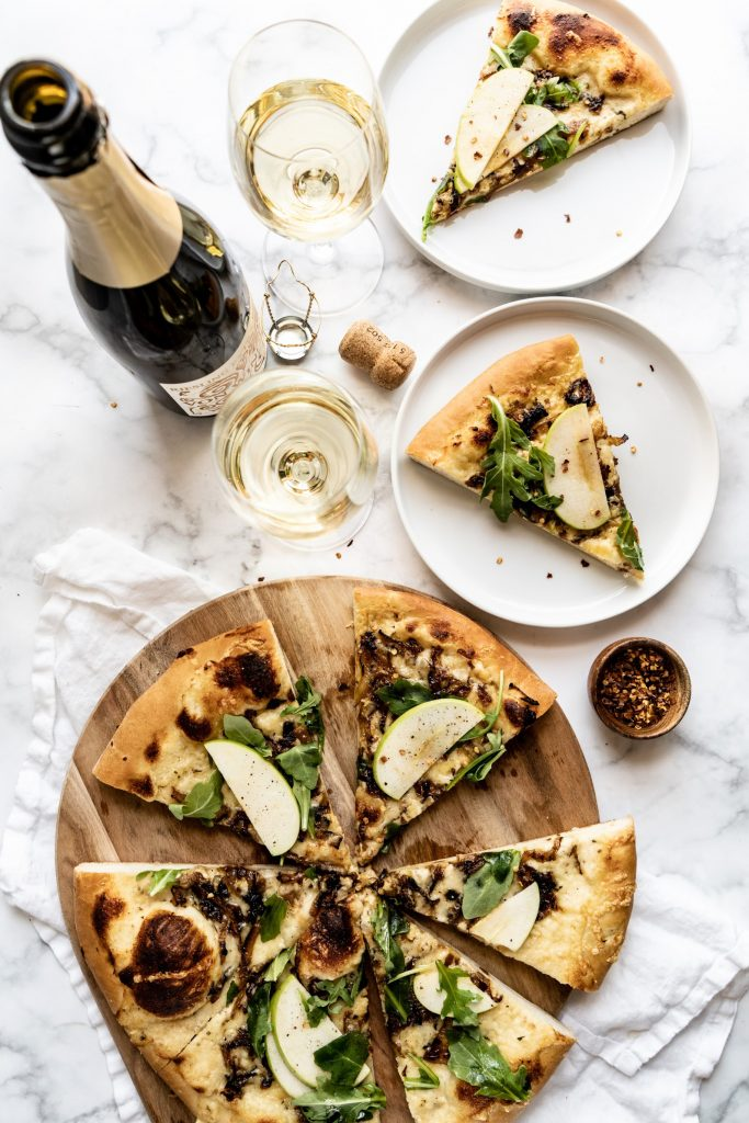 overhead shot of Gruyère and Caramelized Onion pizza on cutting board with two pieces of pizza on plates, two glasses of wine and wine bottle on table