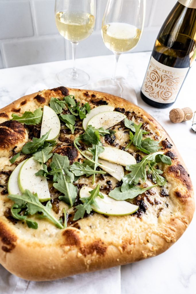 Gruyère and Caramelized Onion pizza on cutting board with two glasses of wine behind