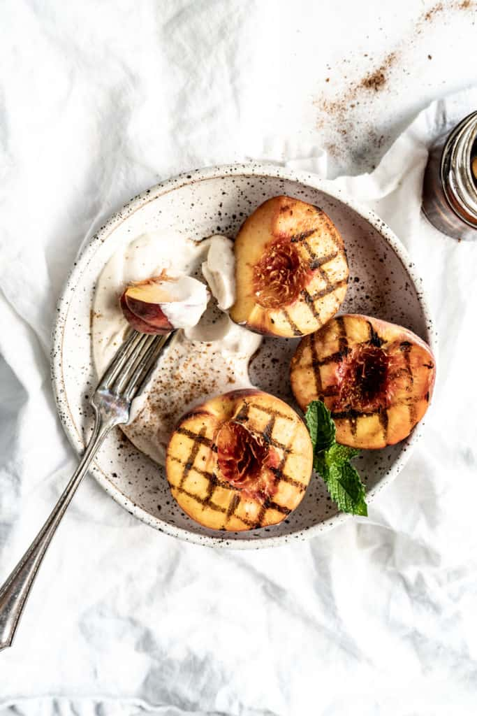 grilled peaches in a bowl with mascarpone cream and fork garnished with mint