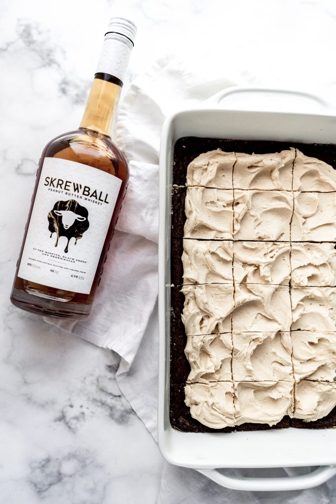 whiskey brownies in pan frosted and sliced with bottle of whiskey laying beside the pan