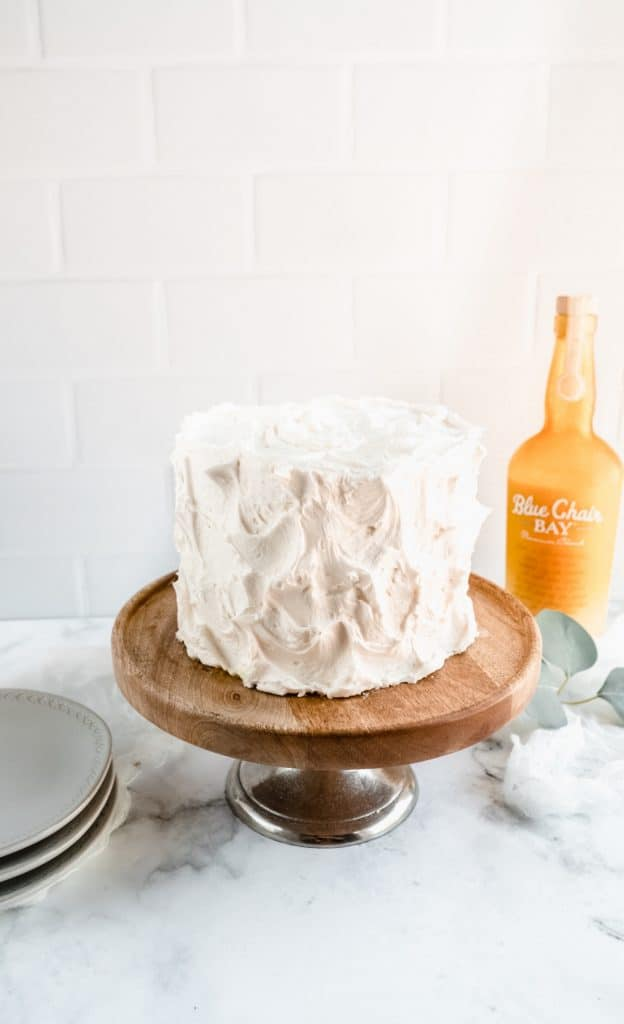 bananas foster cake on cake stand with rum bottle behind