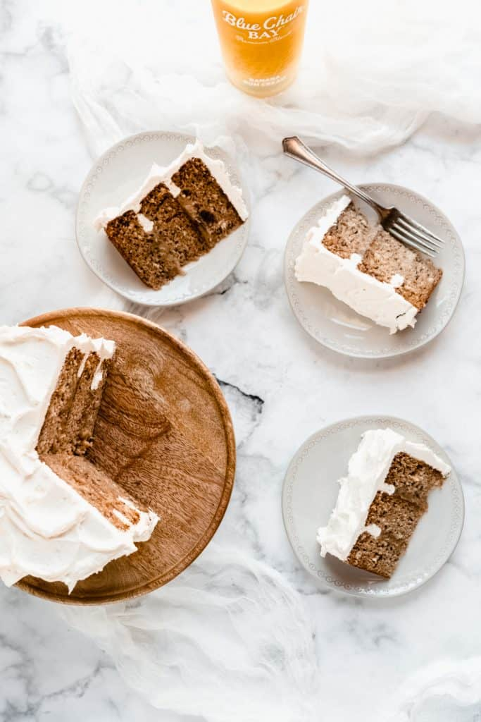 bananas foster cake on stand with three slices on plates