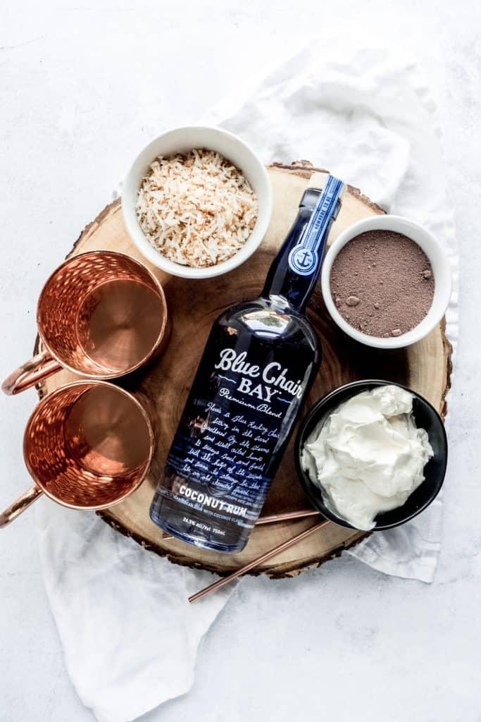boozy coconut hot chocolate ingredients on wood slab
