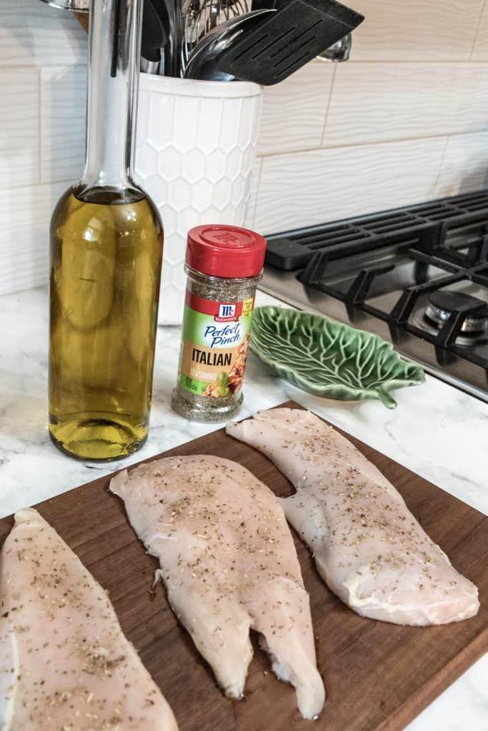 Raw chicken seasoned on cutting board and