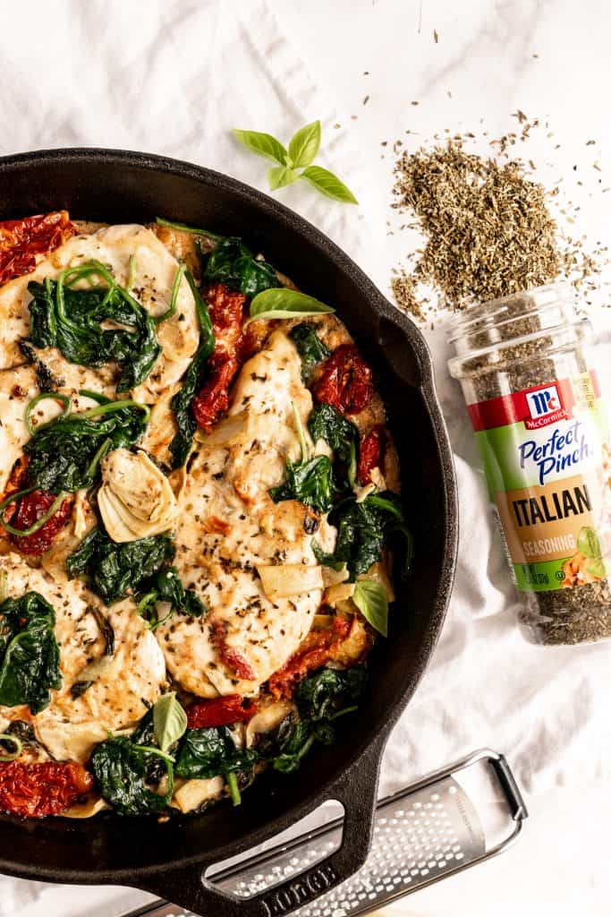finished creamy tuscan chicken in skillet with seasoning bottle and herbs spilling out