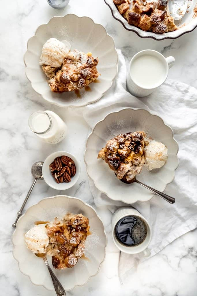 eggnog bread pudding in three small plates with ice cream on marble counter with glasses of milk