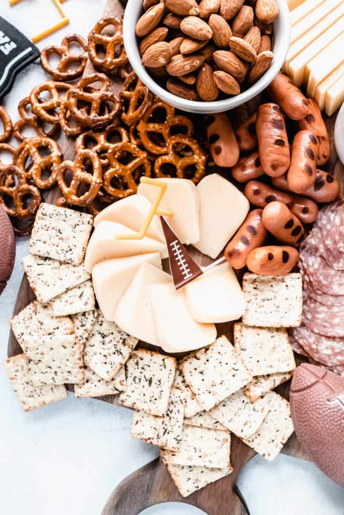 football charcuterie board close up with crackers and smoked gouda and lit'l smokies