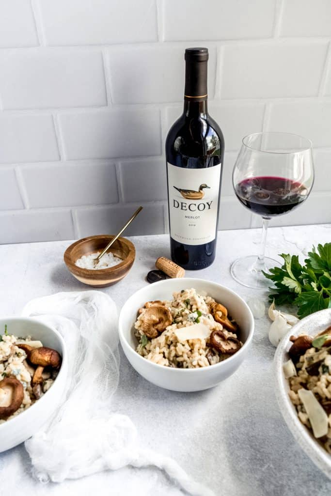 Instant pot Mushroom Gorgonzola risotto in bowl with wine glass and bottle behind