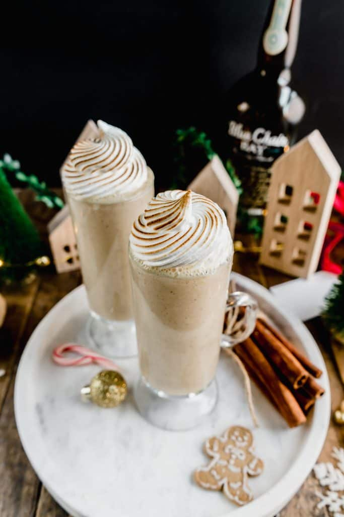 gingerbread coquito on marble serving tray with gingerbread cookies and cinnamon sticks