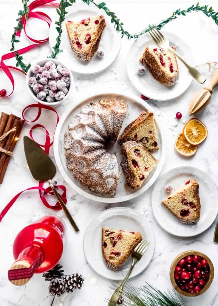 baked cranberry orange rum cake sliced on plates with festive holiday background