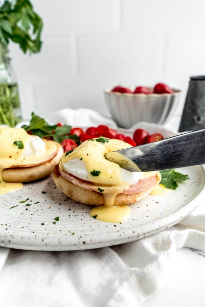 eggs benedict with citrus hollandaise plated and knife cutting into the egg