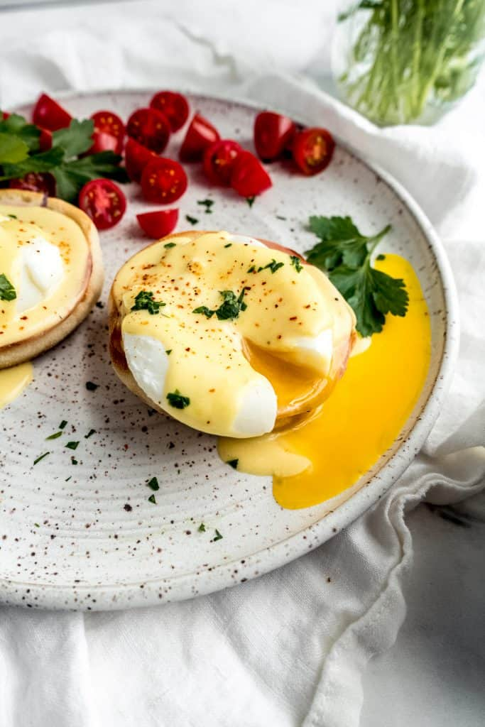 eggs benedict with citrus hollandaise with egg yolk spilling out on plate