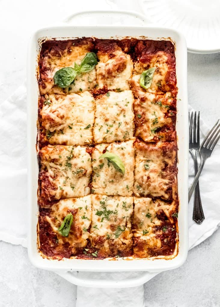 baked lasagna sliced into pieces in baking dish