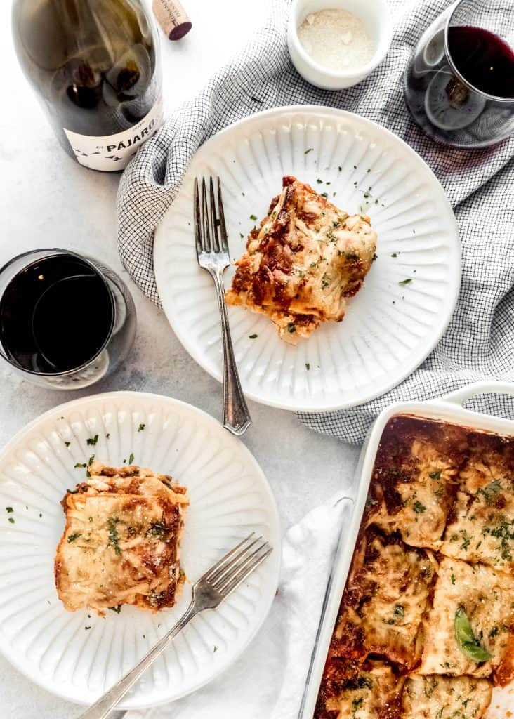 pieces of lasagna on plates with glass of red wine