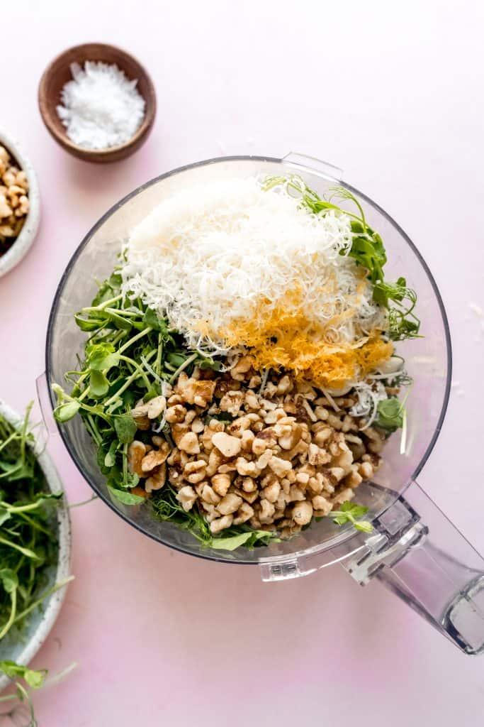 top down shot of pea shoot pesto ingredients in food processor