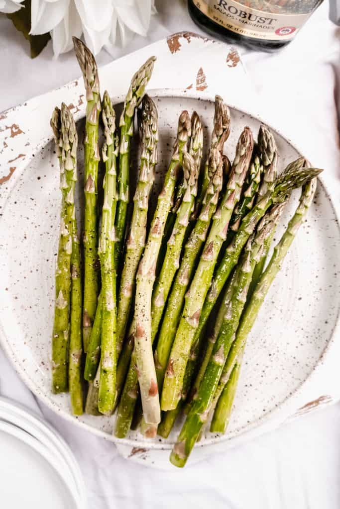 raw asparagus on plate with olive oil and salt and pepper