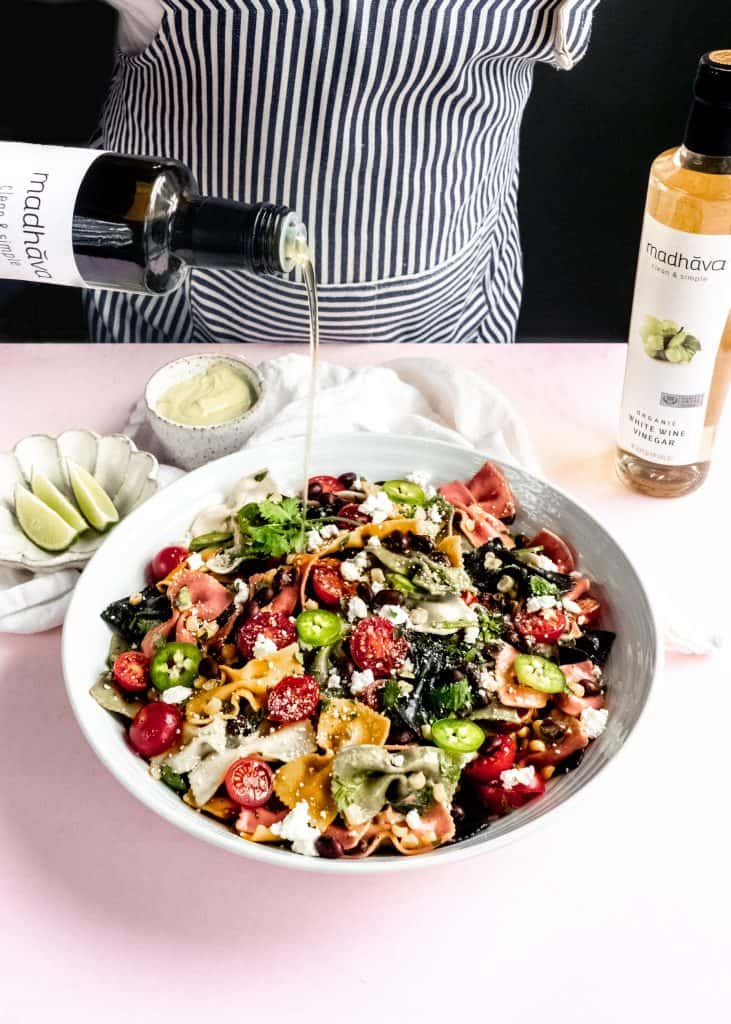 olive oil being poured on mexican pasta salad