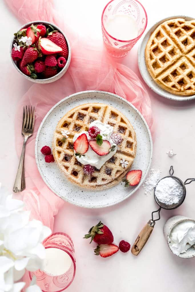 yeast Belgian waffles on plate topped with whipped cream and strawberries dusted with powdered sugar