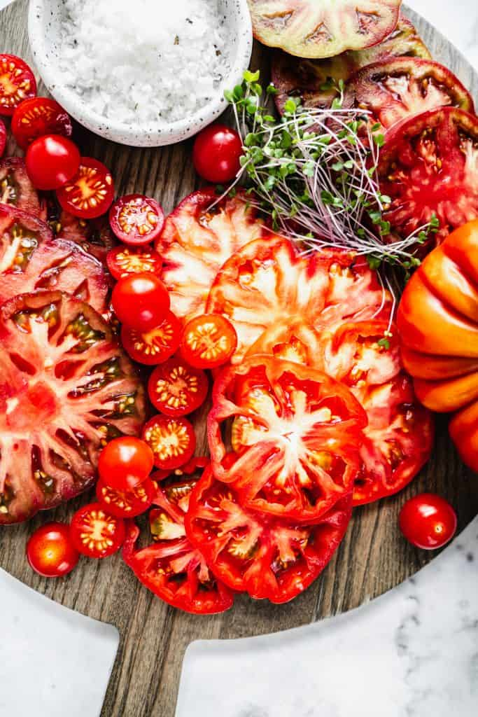 heirloom tomatoes and grape tomatoes sliced on cutting board