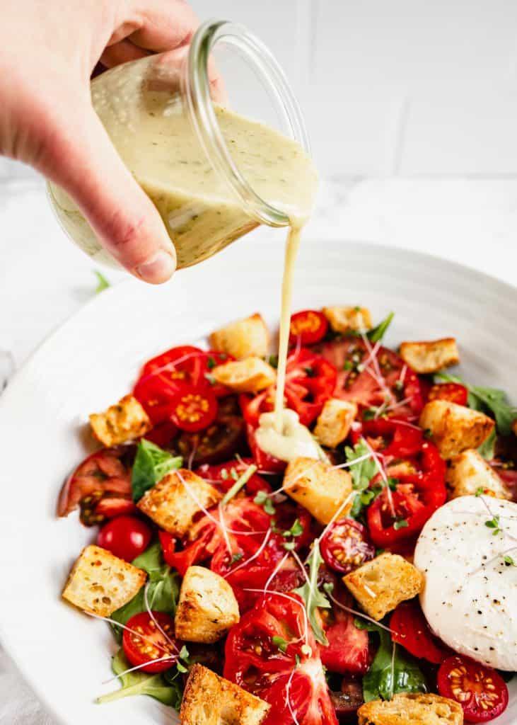 basil vinaigrette poured on panzanella salad