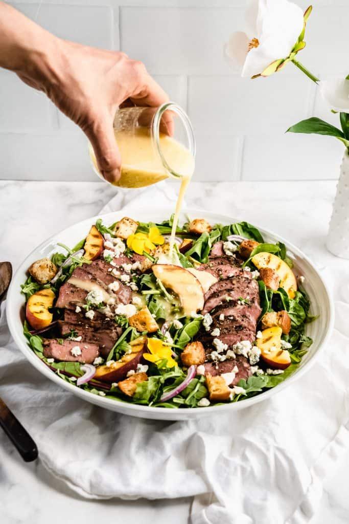 salad dressing being poured on salad