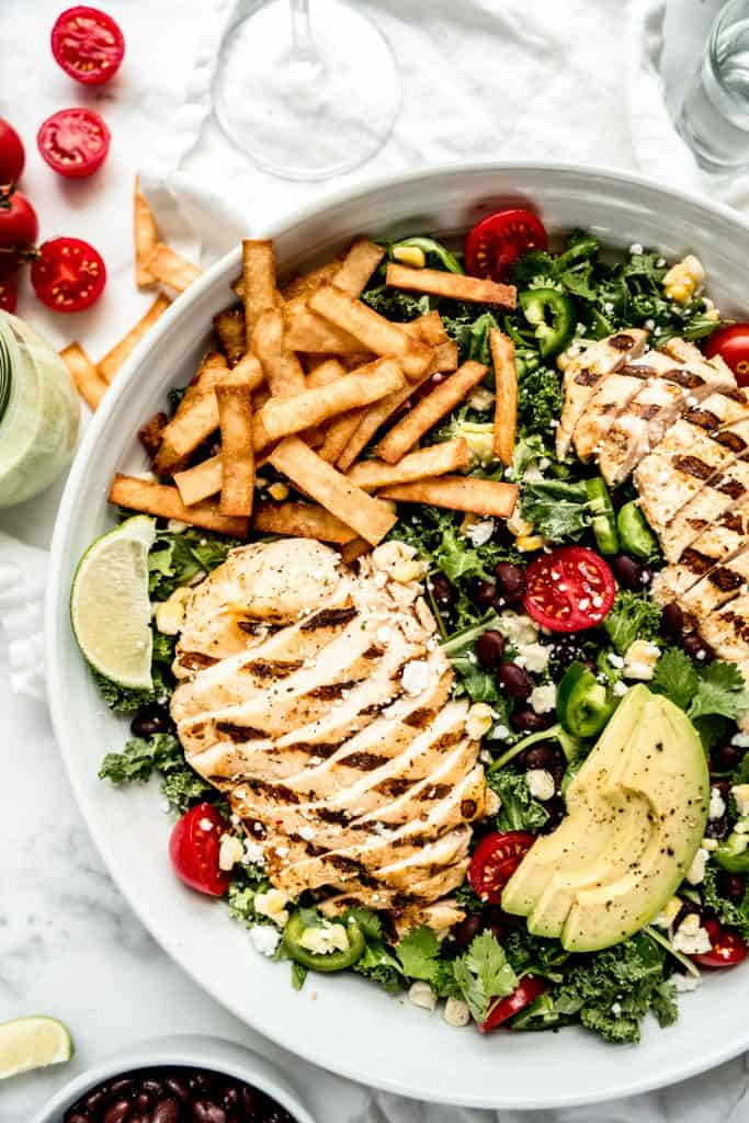 close up of chicken and tortilla strips in grilled chicken taco salad in large bowl